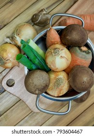 Vegetables and pots, wooden chopping board, onions, mushrooms, carrots