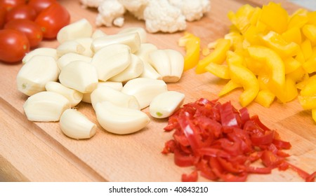 vegetables prepared for pickling - garlic cloves; red chilli; sweet yellow paper; cauliflower florets and plum tomatoes on a wooden chopping board