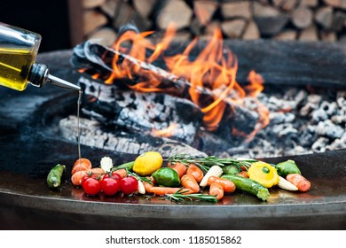 Vegetables preparing on grill. Pepper, onion, zucchini, eggplant, garlic, tomatoes, broccoli. On the background of fire.Selective focus. A man pours olive oil