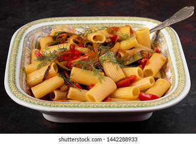 Vegetables rigatoni pasta with fresh dill in a large ceramic bowl. Closeup shot.
