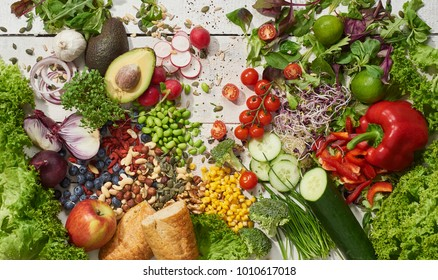 vegetables, salad, berries, nuts and seeds on light wooden background