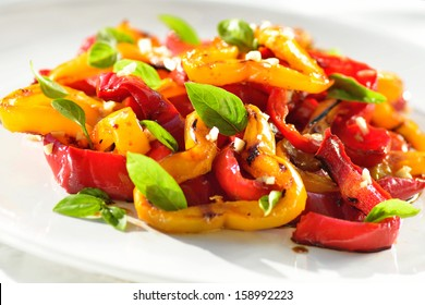 Vegetables salad on white plate. Red and yellow sweet peppers grilled with garlic and basil.Mediterranean cuisine.