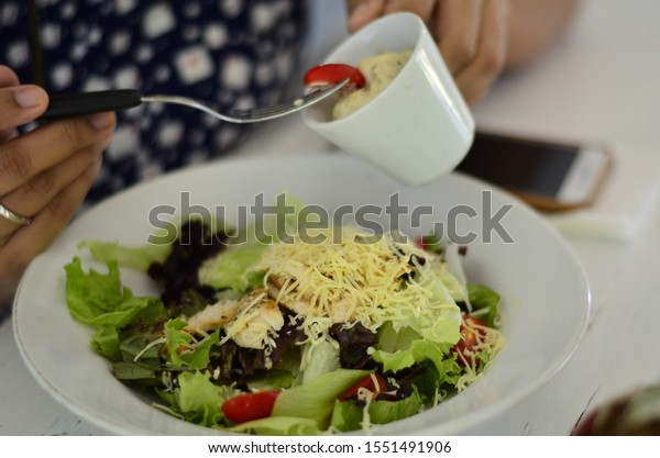 Vegetables salad served with grated cheddar cheese and cream sauce.