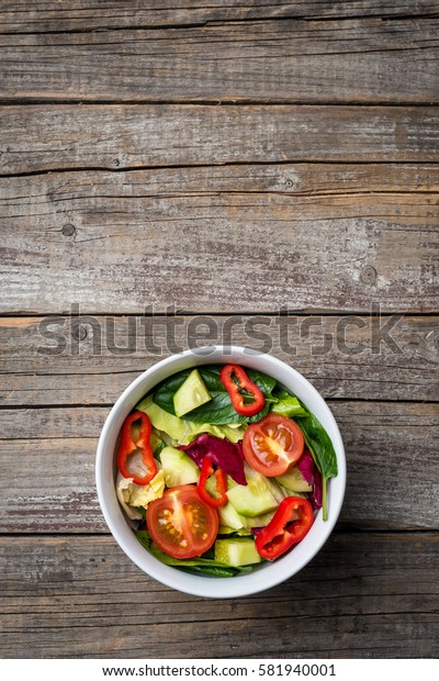 Vegetables salad in white bowl on an old wooden table