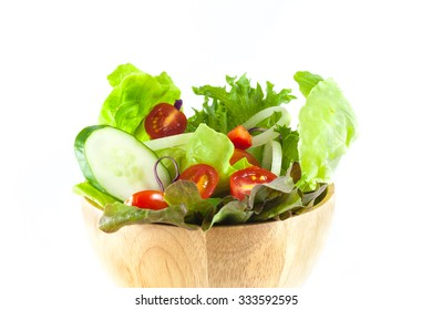 vegetables salad in a wooden bowl isolated on white