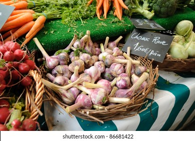 Vegetables are for sale in a farmers market in Paris including garlic, carrots, and radishes. Hand written price signs in French with euro prices are visible.