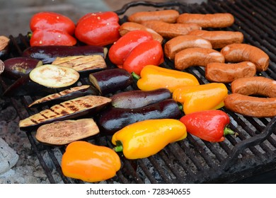 Vegetables and sausages cooked on a grill.