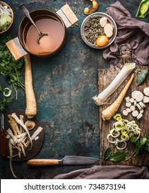 Vegetables soup cooking preparation with parsnip and leek on rustic kitchen table background with ingredients, pot , vegetable broth, knife and cutting board, top view, frame