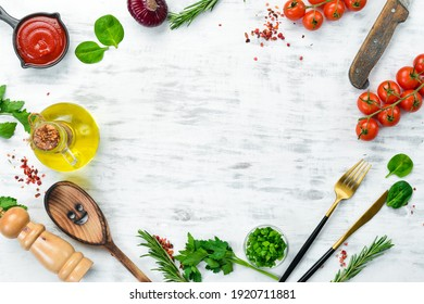 Vegetables, spices and herbs on a white wooden background. Kitchen background. Top view. Free space for text.