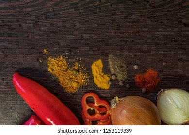 Vegetables and spices on dark wooden background. Vegetarian food, healthy cooking concept