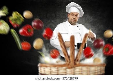Vegetables splash and cook chef on black background