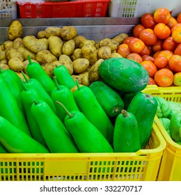 Vegetables stand in Wet Market in Asia with fresh raw ginger, onion, potatoes, tomatoes, calabash, green papaya and chayote. Colorful and healthy concept