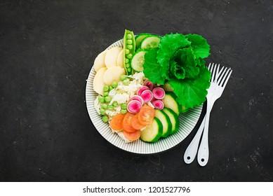 Vegetables summer fruit detox bowl. Vegetarian healthy food. Salads, lettuce leaves, raspberries, green peas, cucumber, carrots, daikon, edible flowers Top View