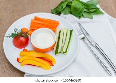 Vegetables - сarrot, tomato, pepper, cucumber and sauce on the white plate