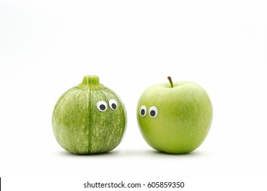 vegetables versus fruit - zucchini and green apple with googly eyes on white background