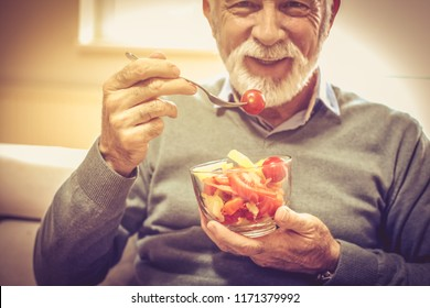 Vegetables are vitamin. Senior man eating vegetable. Close up. Focus is on hands.