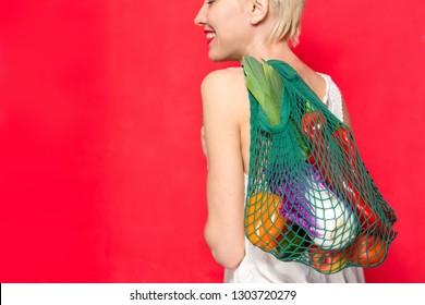 Vegetables, woman, vegetarian, diet, calories, diet food. Beautiful caucasian woman holding net bag with vegetable