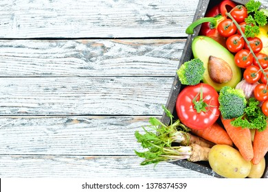 Vegetables in a wooden box. Avocado, cucumber, onion, garlic, tomatoes, carrots, horseradish. Top view. Free space for your text.