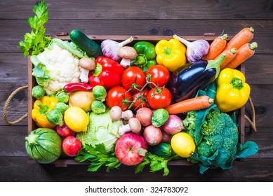 Vegetables in wooden box on dark background.