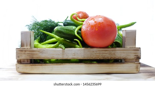 Vegetables in wooden crate  on white background  -tomato, cucumber,  green peppers,  dill and fresh mint