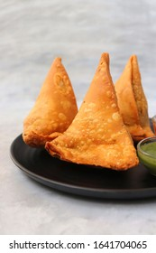 Vegetarian Aloo samosa or samosas. Indian special traditional street food. Famous Indian Punjabi samosa filled with spicy boiled potato mixture. served with green and red chutneys. Copy space.