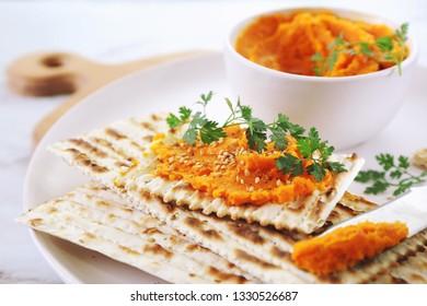 Vegetarian appetizer. Carrot dip on dry bread, sesame dressing on light background