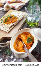 Vegetarian appetizer. Carrot dip on dry bread, sesame dressing and olive oil. Rustic style