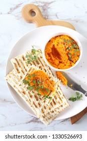 Vegetarian appetizer. Carrot dip on dry bread, sesame dressing. Top view