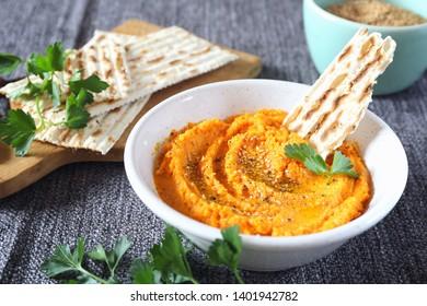 Vegetarian appetizer. Carrot dip on dry bread, sesame dressing and parsley on dark background
