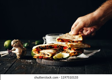 Vegetarian Appetizer on dark wooden table: quesadilla with vegetables and cheese on dark background