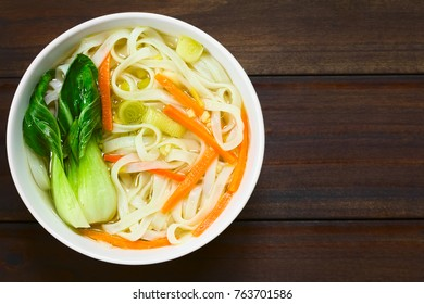 Vegetarian Asian rice noodle soup with bok choy, carrots and spring onion, photographed overhead on dark wood with natural light (Selective Focus, Focus on the top of the soup)