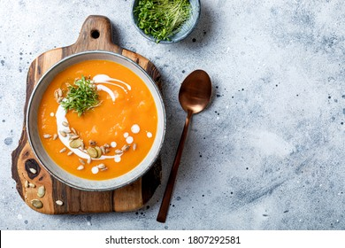 Vegetarian autumn pumpkin and carrot soup with cream, seeds and cilantro micro greens. Comfort food, fall and winter healthy slow food concept