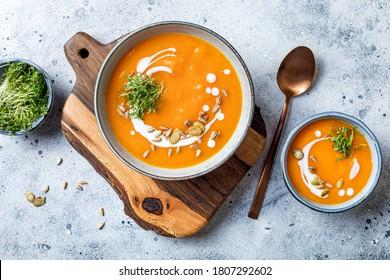Vegetarier Herbstkürbis und Karottensuppe mit Sahne, Samen und Mikropflanzen. Komfortnahrung, Herbst und Winter gesundes Langsames Lebensmittelkonzept