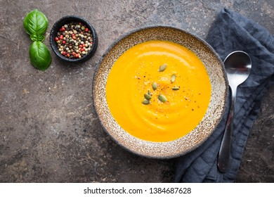 Vegetarian autumn pumpkin cream soup with seeds on dark background, top view
