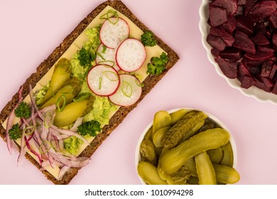 Vegetarian Avocado and Cheese With Radishes and Gherkins Rye Bread Open Faced Sandwich Against A Lilac Background,