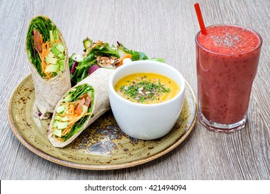 vegetarian avocado tortilla wrap sandwich and cup of decorated soup on rustic plate fresh fruit strawberry juice smoothie shake