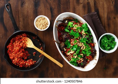 Vegetarian baked stuffed eggplant with lentils, tomatoes and nuts on wooden table top view. Healthy vegetarian food