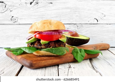 Vegetarian bean and sweet potato burger with avocado and spinach against a rustic white wood background