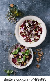 Vegetarian beetroot carpaccio salads with radish, basil, olive oil, goat cheese, walnuts, pine and sprouts in two plate over blue texture background. Top view, space. Healthy eating