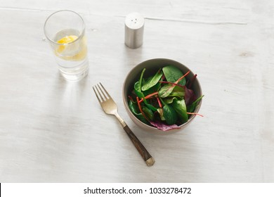 Vegetarian biodynamic food concept. Bowl of salad with spinach leaves and beet leaves on white wooden table with glass of water with lemon. Top view