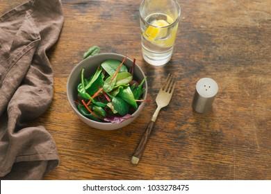 Vegetarian biodynamic food concept. Bowl of salad with spinach leaves and beet leaves on dark wooden table with glass of water with lemon. Top view