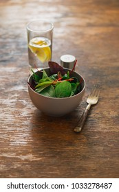 Vegetarian biodynamic food concept. Bowl of salad with spinach leaves and beet leaves on wooden table with water with lemon