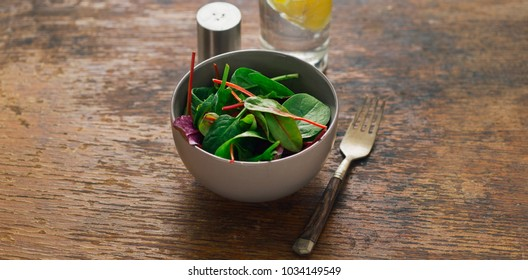 Vegetarian biodynamic food concept. Bowl of salad with spinach leaves and beet leaves on dark wooden table with glass of water with lemon