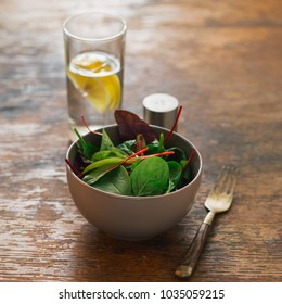 Vegetarian biodynamic food concept. Close up bowl of salad with spinach leaves and beet leaves on dark wooden table with glass of water with lemon
