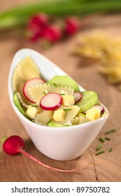 Vegetarian bow tie pasta salad with cucumber, radish, cheese and chives (Selective Focus, Focus on the front of the radish slice in the middle and the cucumber slice on the right)