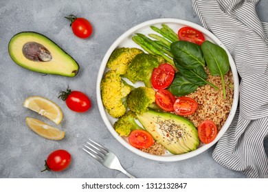 vegetarian breakfast. quinoa with vegetables: broccoli, asparagus, tomatoes, avocado and spinach in a white plate on a gray background. view from above