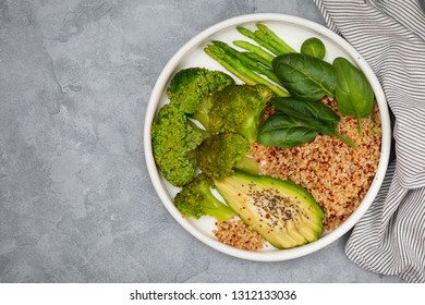 vegetarian breakfast. quinoa with vegetables: broccoli, asparagus,  avocado and spinach in a white plate on a gray background. view from above