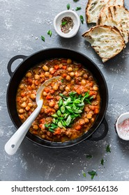 Vegetarian buffalo chickpea chili with mushrooms in a pan on a gray background, top view. Healthy vegetarian food concept