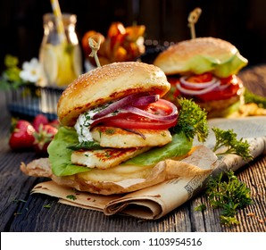 Vegetarian burger with grilled halloumi cheese, fresh lettuce, tomato, cucumber and onion with the addition of yoghurt mint sauce on a wooden rustic table