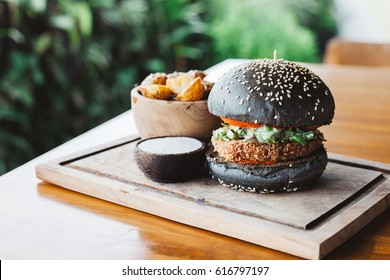 Vegetarian burger made with black charcoal bun with sesame served with potato wedges and sauce on wooden rustic table